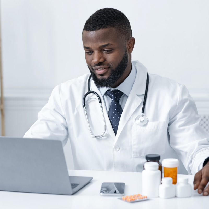 Concentrated african doctor checking on new pills